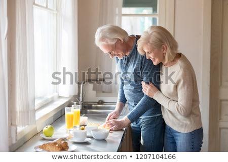 senior couple cooking dishes in kitchen stock photo © kzenon