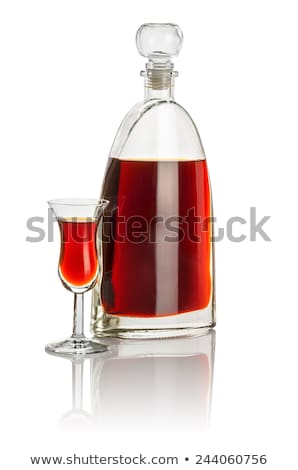 Carafe and high shot glass filled with brown liquid Stock photo © Zerbor