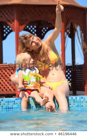 beautiful woman with blond little girl sitting on ledge pool ope Stock photo © Paha_L