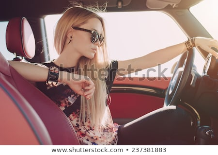 beautiful young blond girl in a black vintage car stock photo © lithian
