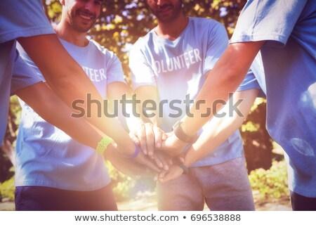 Volunteers forming a hand stack in the park Stock photo © wavebreak_media