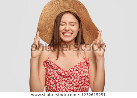 hopeful young woman gesturing with fingers stock photo © deandrobot