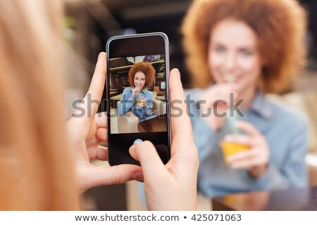 the girl takes a photo on the phone of a young pretty woman with a bouquet of fresh flowers on a gra stock photo © artjazz