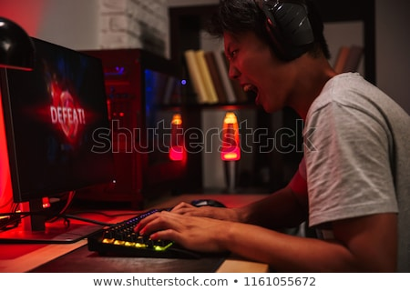 Portrait of upset asian gamer boy losing while playing video gam Stock photo © deandrobot