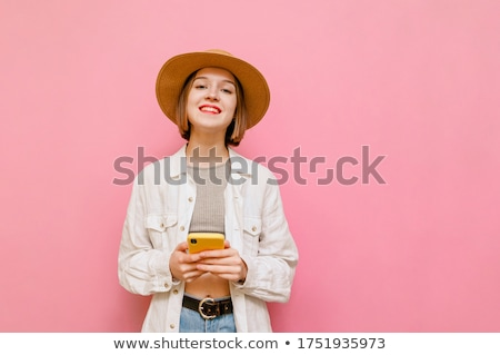 A teenage girl in light clothes posing on a pink background. Stock photo © Traimak