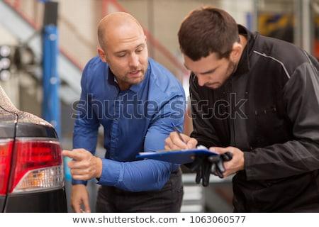 mechanic and customer looking at car taillight stock photo © dolgachov