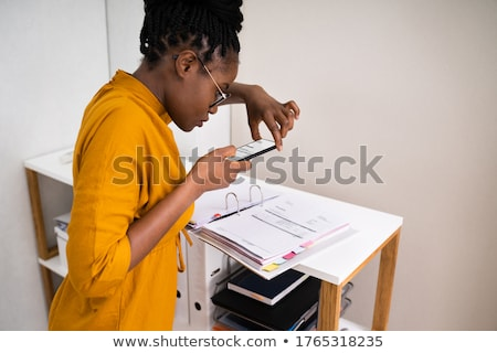 A young girl in the office takes out a folder with documents from the shelter. Stock photo © Traimak