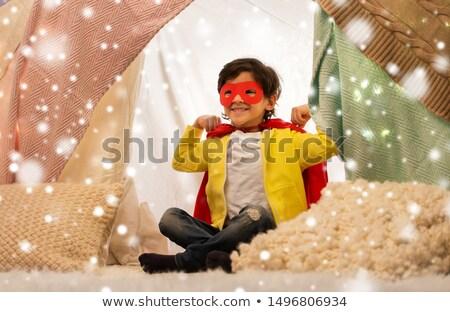 happy boy in super hero cape in kids tent at home Stock photo © dolgachov