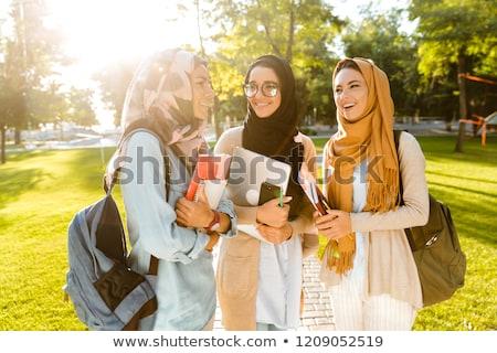 Happy friends muslim sisters women walking outdoors holding books. Stock photo © deandrobot
