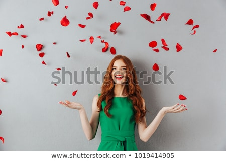beautiful happy young woman over red rose petals Stock photo © dolgachov