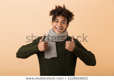 Portrait of joyous african american guy wearing sweater and scar Stock photo © deandrobot