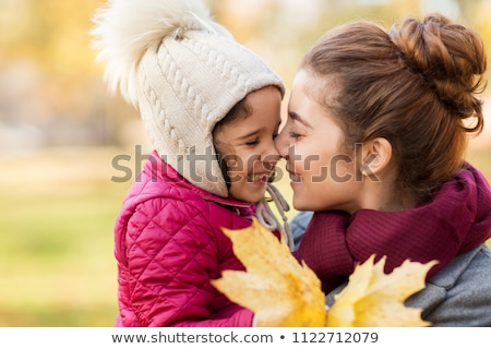 mother kissing little daughter in autumn stock photo © dolgachov