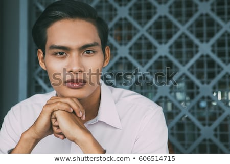 closeup of a young businessman holding hand on chin Stock photo © feedough