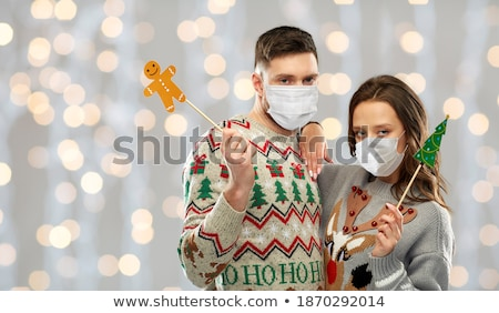 couple with party props over christmas tree lights Stock photo © dolgachov
