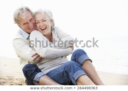 smiling couple hugging on autumn beach stock photo © dolgachov