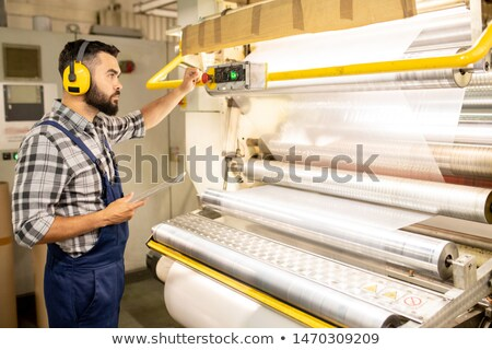 Serious young engineer of chemical production factory taking control of machine Stock photo © pressmaster