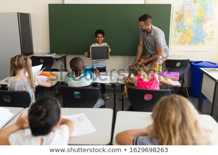 Front view of happy schoolboy holding slate board and standing at greenboard in classroom of element Stock photo © wavebreak_media