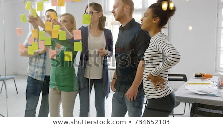 creative team with scheme on office glass board stock photo © dolgachov