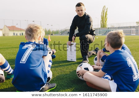 Young Coach Explaining Soccer Positions and Match Tactics to Youth. Kids Football Team Coaching. Chi Stock photo © matimix