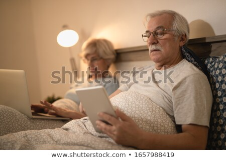 man reading in bed while his wife surfs the internet stock photo © photography33