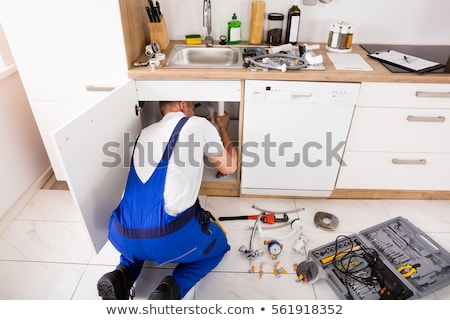 Stock photo: A kneeled plumber.