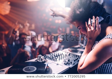 Stock photo: Female DJ at the turntable in Club