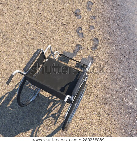 Empty Wheelchair On A Beach Of Sand With Footprints Concept Background Stok fotoğraf © denisgo