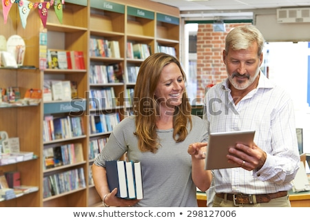 ストックフォト: Male And Female Owners Of Bookstore Using Digital Tablet