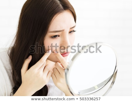 young woman squeezing pimple on her face Stock photo © dolgachov