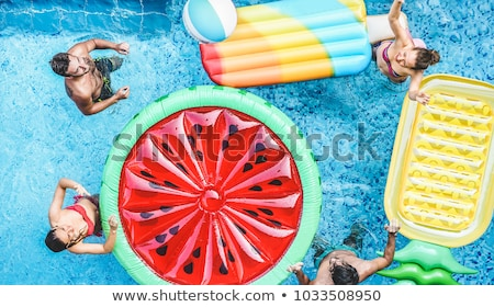 Happy young couple floating on mattress in pool Stock photo © dash