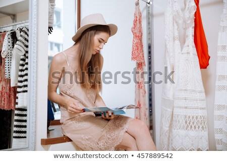 Alegre mulher leitura revista roupa compras Foto stock © deandrobot