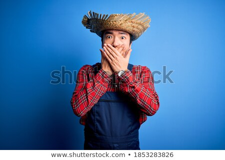 portrait of a shocked young man in straw hat stock photo © deandrobot