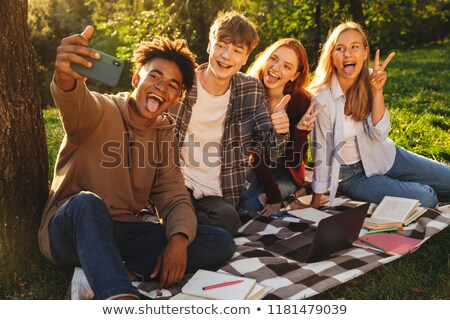 Grupo encantado estudantes lição de casa juntos parque Foto stock © deandrobot