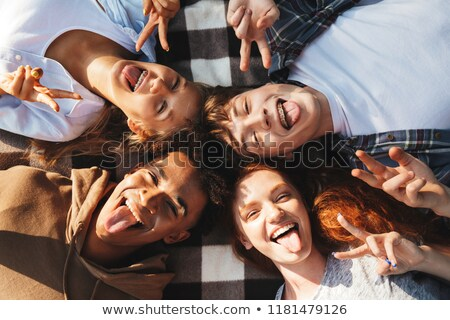Image of four joyous people men and women laughing, and lying on Stock photo © deandrobot