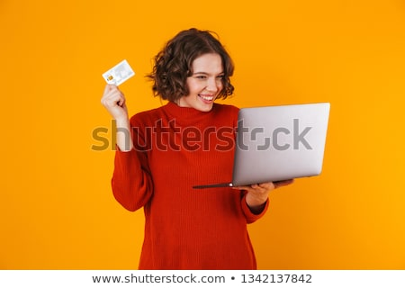 Image of caucasian woman 20s holding silver laptop and credit ca Stock photo © deandrobot
