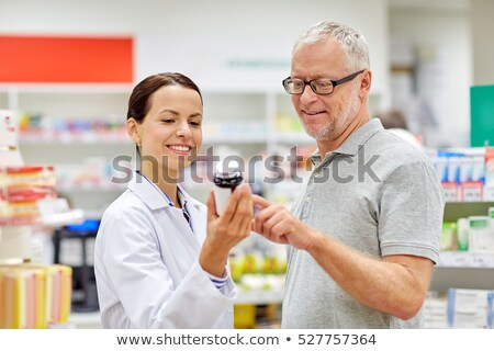 apothecary showing drug to senior man at pharmacy Stock photo © dolgachov