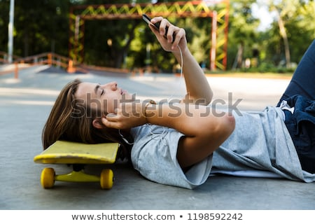 Attractive young guy spending time at the skate park Stock photo © deandrobot