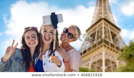 friends taking selfie by monopod over eiffel tower stock photo © dolgachov