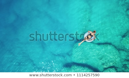 Aerial view of young woman swimming on the swim ring in blue sea Stock photo © denbelitsky