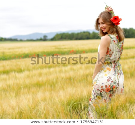 happy girl in a yellow dress staying in the field of flowering rape nature blooms rape seed field stock photo © elenabatkova