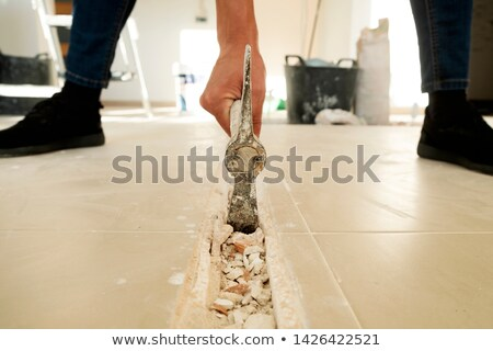 man making a groove in a tiled floor Stock photo © nito
