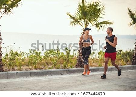 カップル スポーツ 服 を実行して ビーチ パス ストックフォト © dolgachov