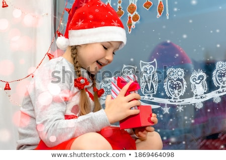 girl with christmas gift sitting on sill at window Stock photo © dolgachov