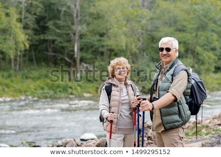 Active aged spouses with backpacks and trekking sticks enjoying summer trip Stock photo © pressmaster