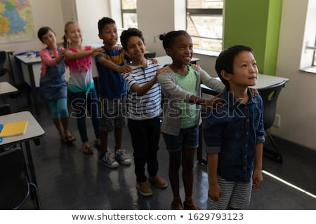 Side view of school kids standing in row with their hands on shoulder in classroom of elementary sch Stock photo © wavebreak_media