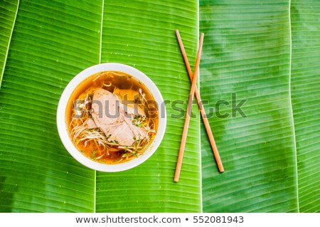 A bowl of Traditional Vietnamese beef soup Pho Bo on banana leaf background. Stock photo © galitskaya