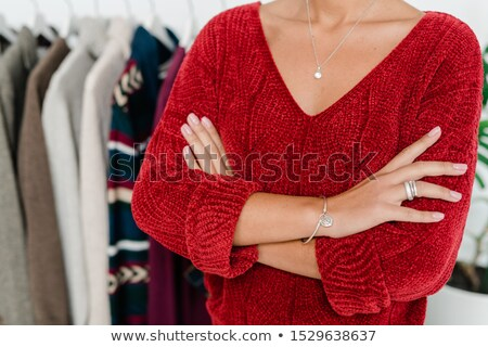 Young elegant woman in red knitted pullover crossing arms by chest Stock photo © pressmaster