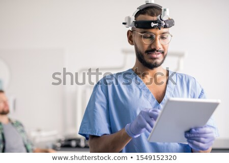Clinician in uniform and medical equipment on head scrolling through online data Stock photo © pressmaster