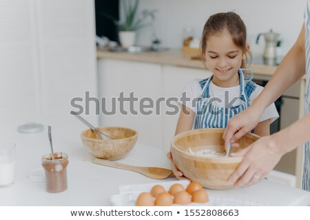 Smiling little girl helper holds big bowl, looks how mother is mixing eggs with flour, prepare tasty Stock photo © vkstudio