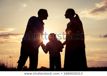 Happy family standing in the park at the sunset time. stock photo © altanaka